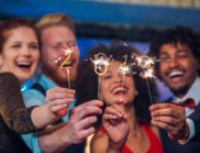 Smiling people holding sparklers